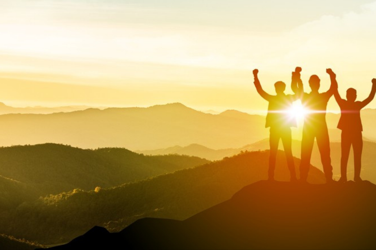 PEOPLE REACHING TOP OF MOUNTAIN SUCCESS
